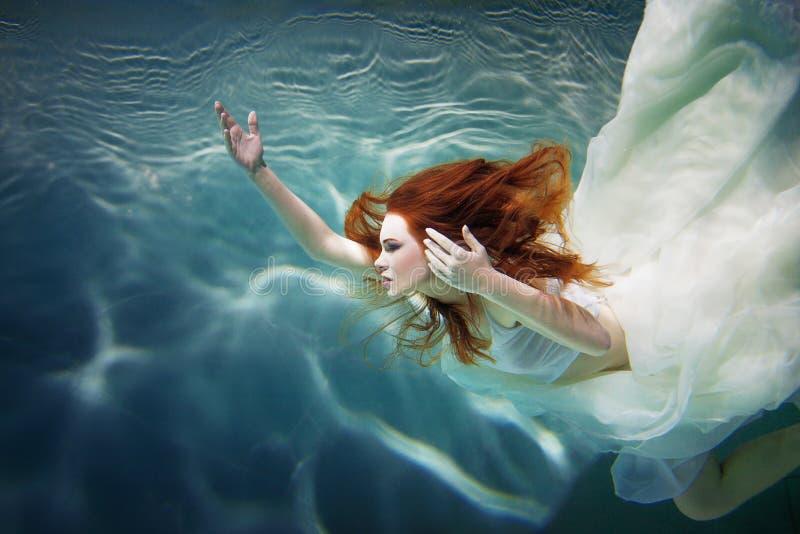 Muchacha subacuática Mujer pelirroja hermosa en un vestido blanco, nadando debajo del agua imagen de archivo libre de regalías