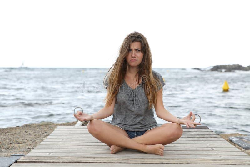 Muchacha subrayada que intenta hacer ejercicios de la yoga fotos de archivo libres de regalías