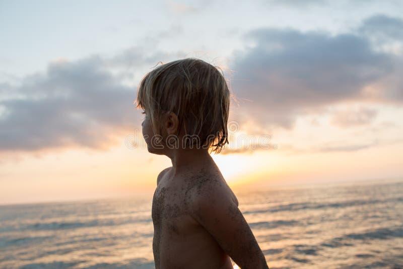 Muchacha sucia del niño de la arena joven que mira la orilla ausente de la playa Luz caliente de la puesta del sol El viaje del v imagenes de archivo