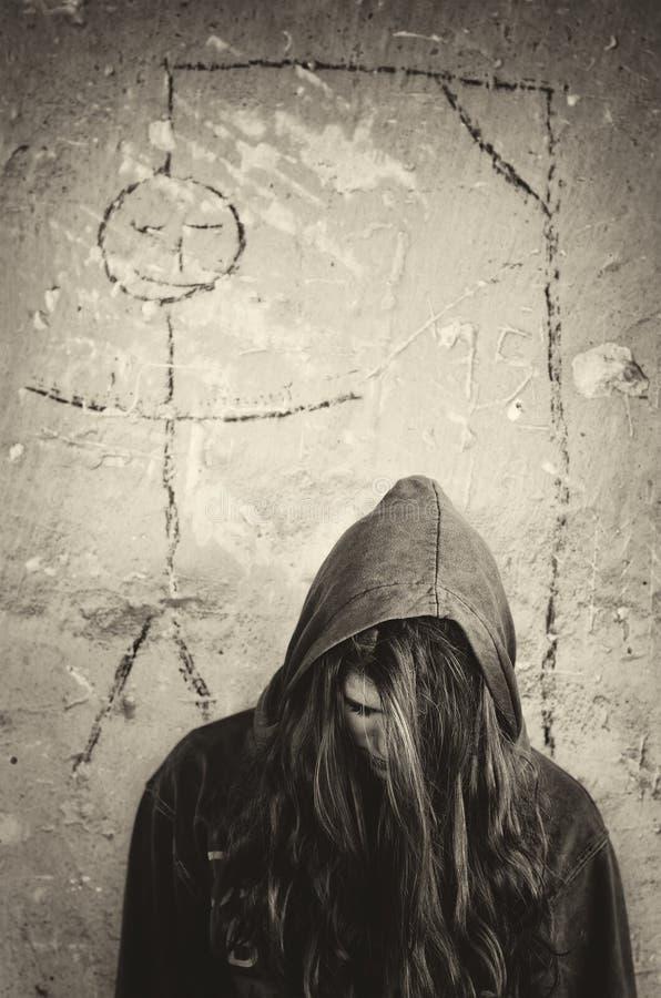 Muchacha suicida deprimida que se coloca debajo del dibujo de la horca foto de archivo libre de regalías