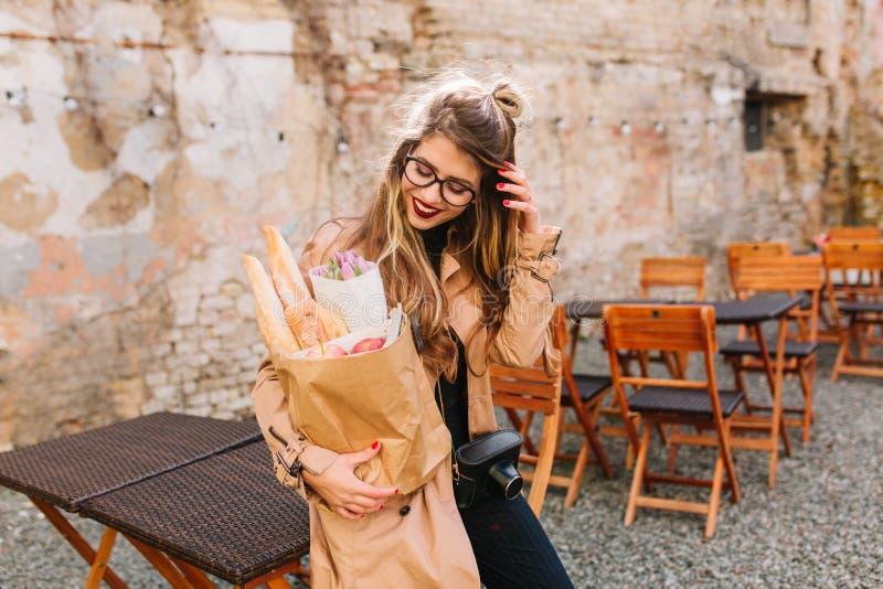 Muchacha tímida agradable con miradas largas del pelo en la situación del bolso de la panadería en restaurante al aire libre dela fotos de archivo