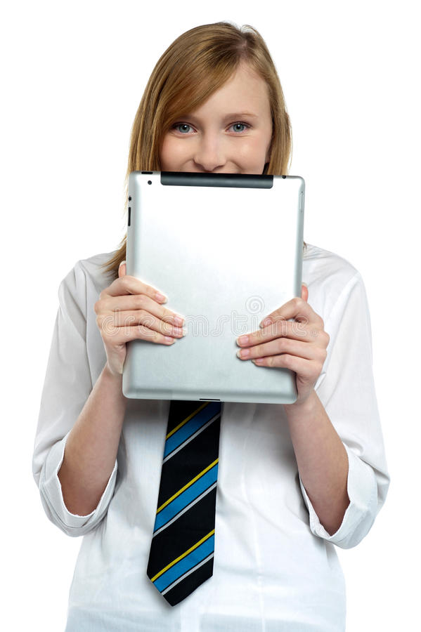 Muchacha tímida que oculta su cara con un dispositivo de la tablilla imagen de archivo