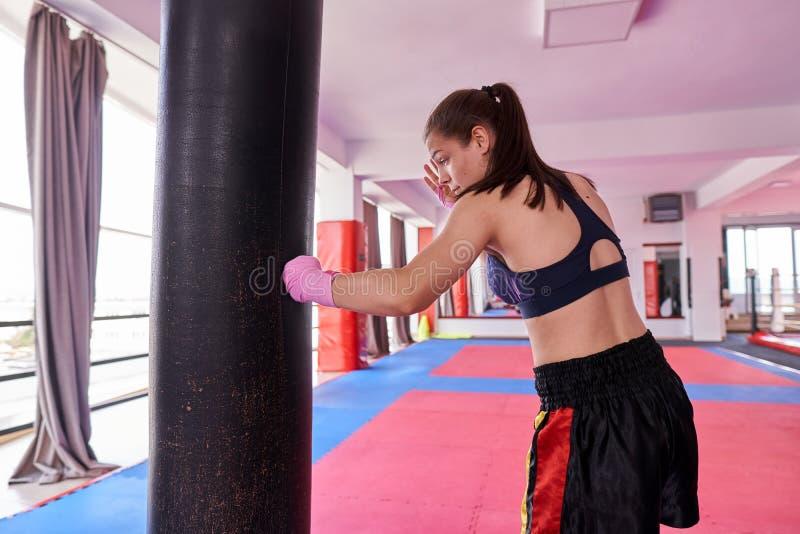 Muchacha tailandesa de Muay que practica con el bolso pesado imagenes de archivo