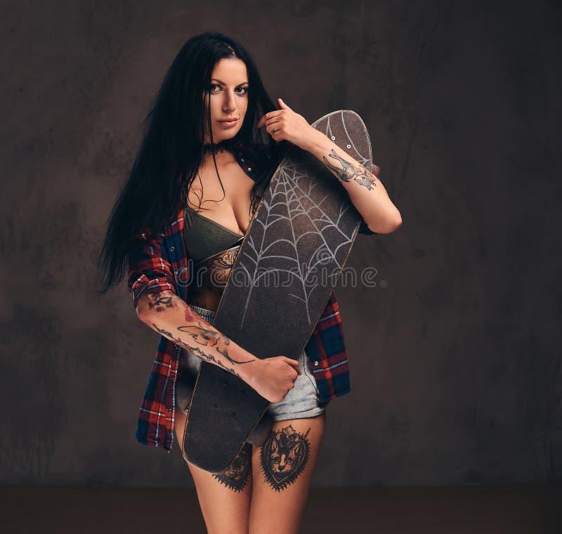 Muchacha tatuada atractiva que lleva una camisa a cuadros desabrochada roja y los pantalones cortos que sostienen un monopatín qu foto de archivo libre de regalías
