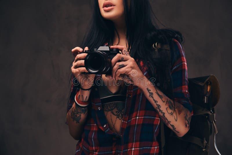 Muchacha tatuada del inconformista que lleva una camisa comprobada desabrochada roja que sostiene una cámara en un fondo oscuro imágenes de archivo libres de regalías