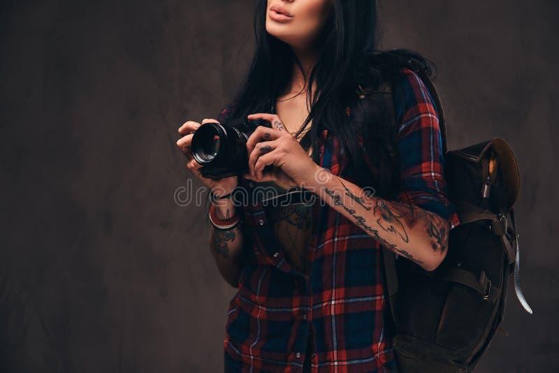 Muchacha tatuada del inconformista que lleva una camisa comprobada desabrochada roja que sostiene una cámara en un fondo oscuro imagen de archivo libre de regalías