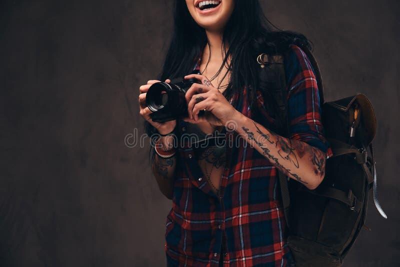 Muchacha tatuada del inconformista que lleva una camisa comprobada desabrochada roja que sostiene una cámara en un fondo oscuro imagenes de archivo