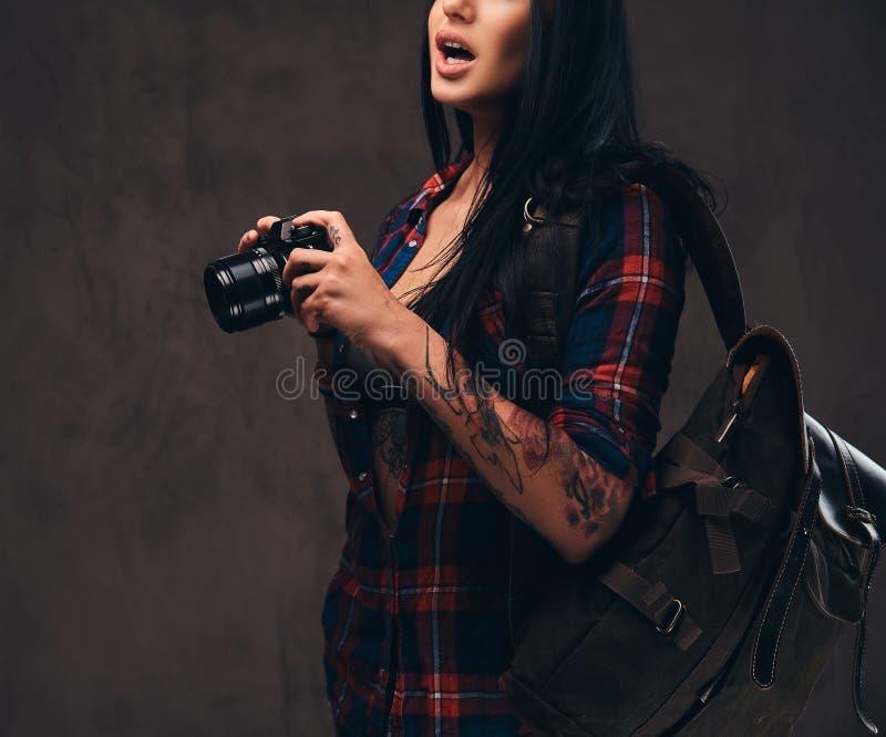 Muchacha tatuada del inconformista que lleva una camisa comprobada desabrochada roja que sostiene una cámara en un fondo oscuro foto de archivo