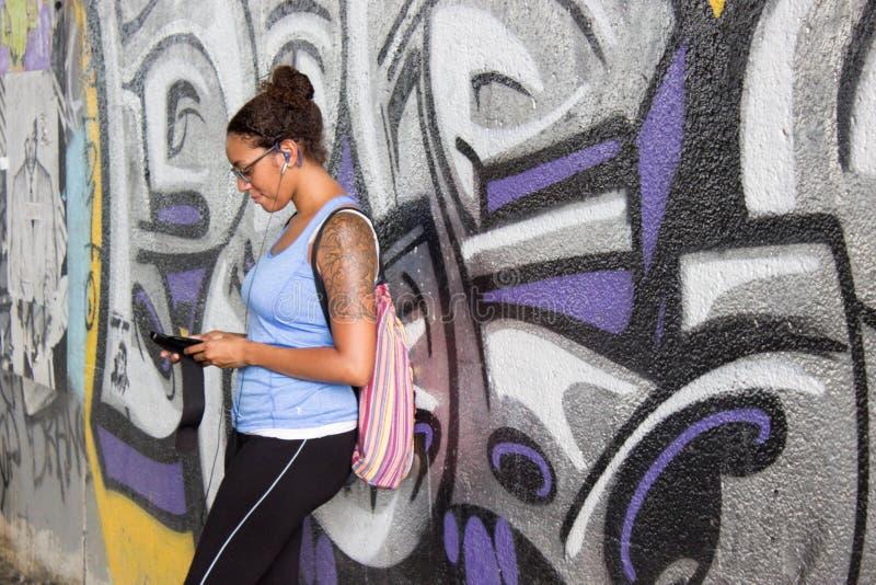 Muchacha tatuada en inclinarse en la pared de la pintada fotos de archivo libres de regalías