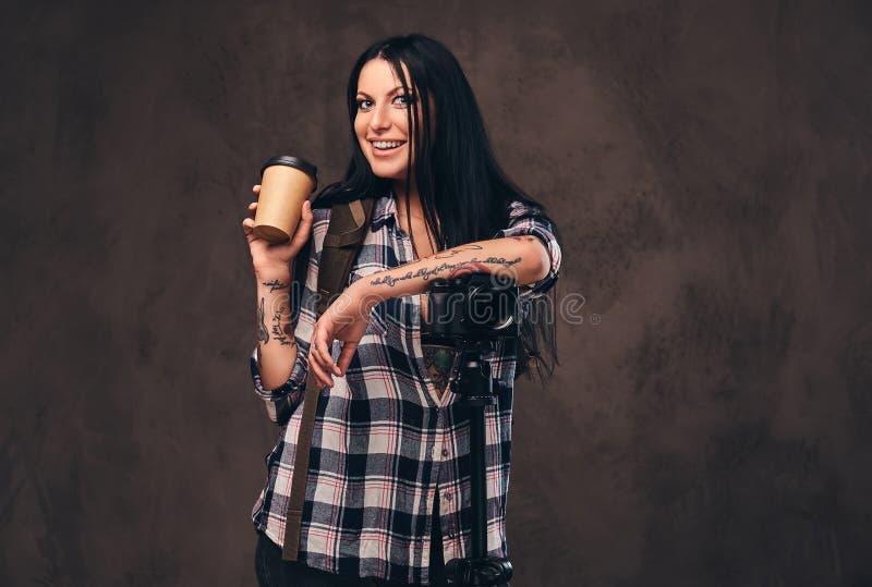 Muchacha tatuada que sostiene un café para llevar mientras que se inclina en una cámara en un estudio foto de archivo