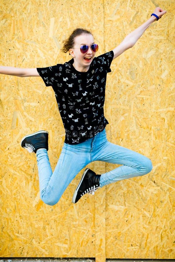 Muchacha teenaged joven que salta delante de la cerca del PA de madera del mdf fotos de archivo