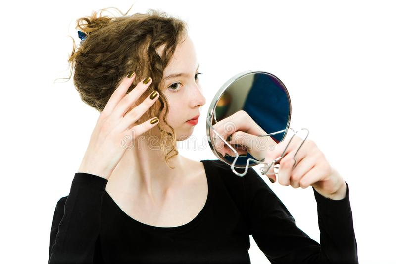 Muchacha Teenaged que comprueba mirada en espejo sus pelos rubios rizados - para ser perfecto imagenes de archivo