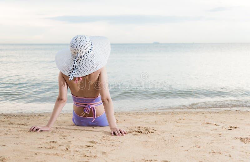 Muchacha trasera de la mujer que se sienta en la playa tropical fotos de archivo libres de regalías