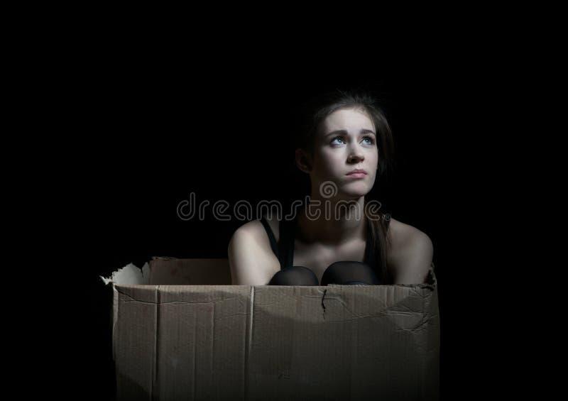 Muchacha trastornada que plantea sentarse en caja de cartón foto de archivo