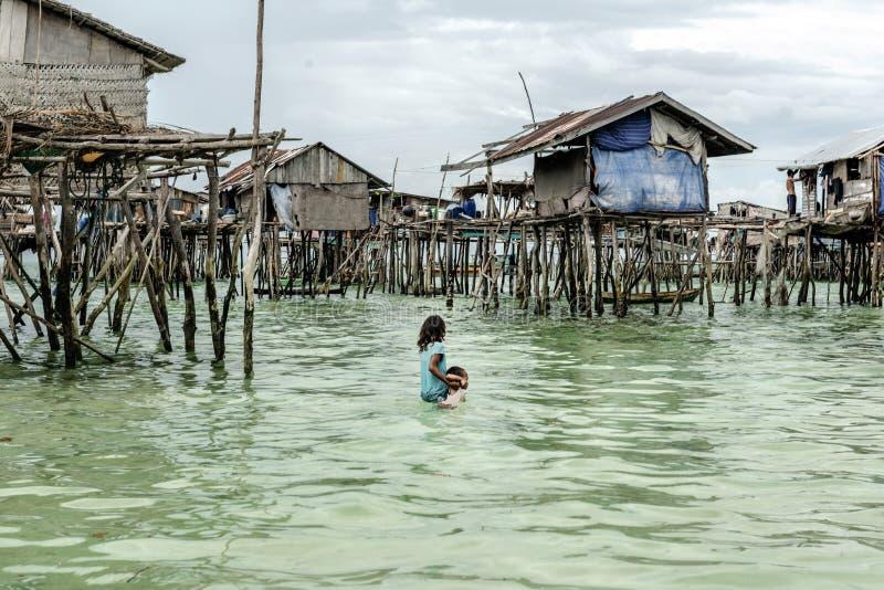 Muchacha tribal de Bajau que lleva a su hermano a su hogar antes de que él consiga hundido en el mar, Sabah Semporna, Malasia foto de archivo