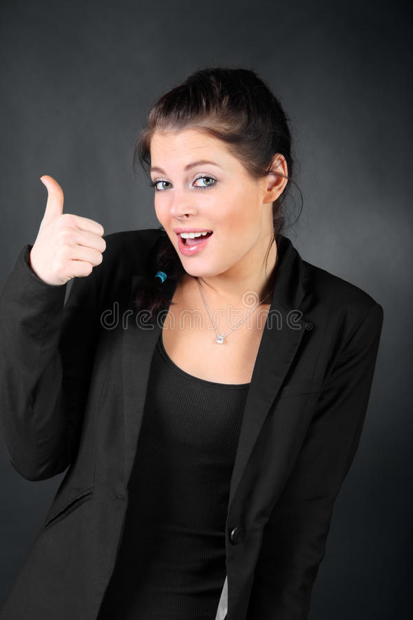 Muchacha triguena en dedo grande de la demostración de la capa fotos de archivo