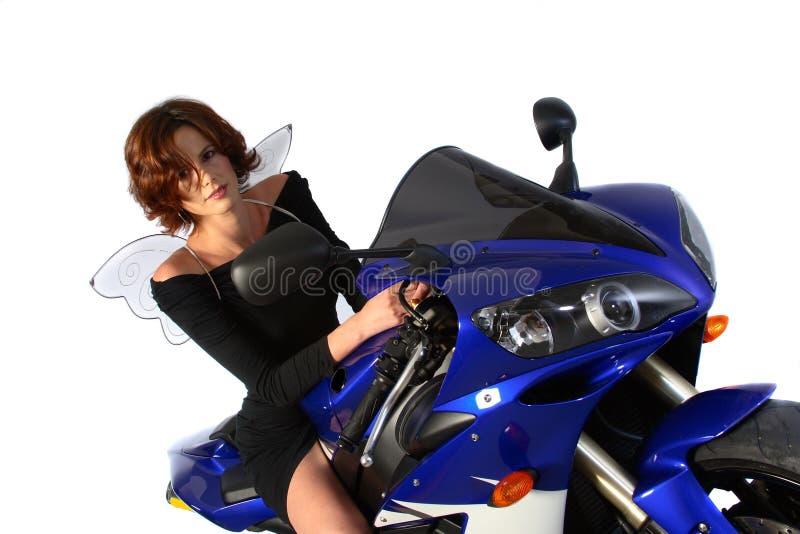 Muchacha triguena en la alineada y las alas del negro de la motocicleta fotografía de archivo libre de regalías
