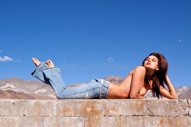 Muchacha triguena hermosa que pone en un muro de cemento fotos de archivo libres de regalías
