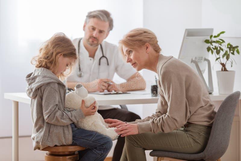 Muchacha triste con el oso de peluche y la abuela preocupante en la oficina del pediatra imagen de archivo