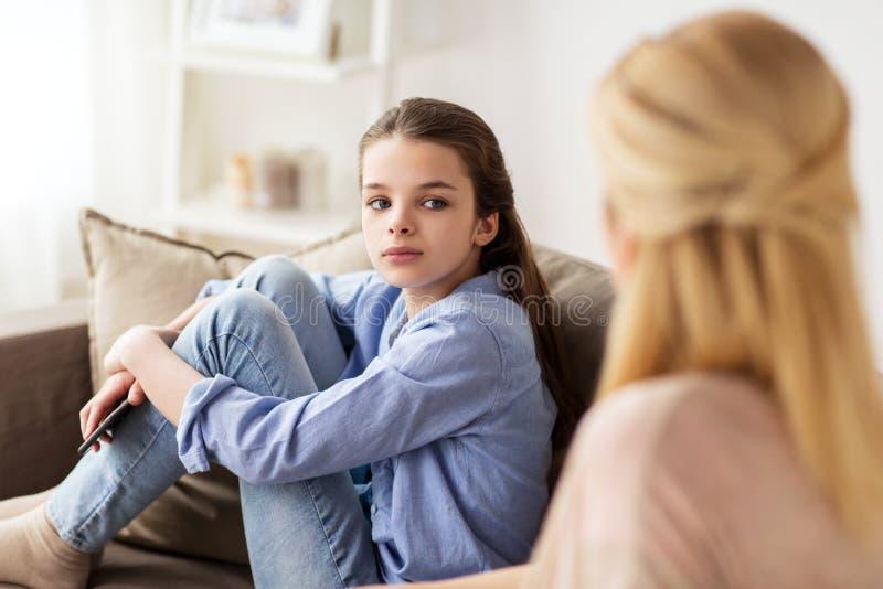 Muchacha triste con la madre que se sienta en el sofá en casa imagenes de archivo
