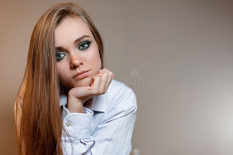 Muchacha triste en camisa en fondo gris imagenes de archivo
