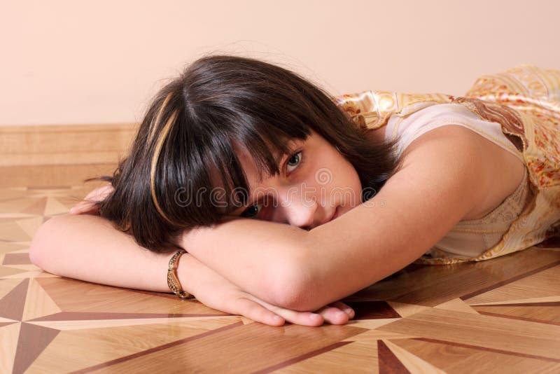 Muchacha triste en suelo imagen de archivo
