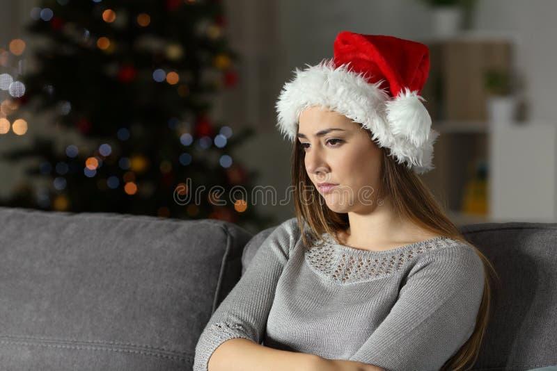 Muchacha triste en tiempo de la Navidad en la noche foto de archivo