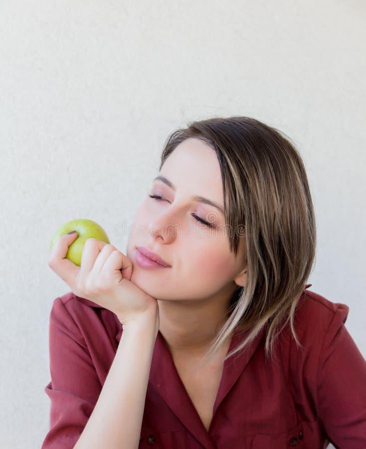 Muchacha triste hermosa con la manzana en la chaqueta roja o imagen de archivo libre de regalías