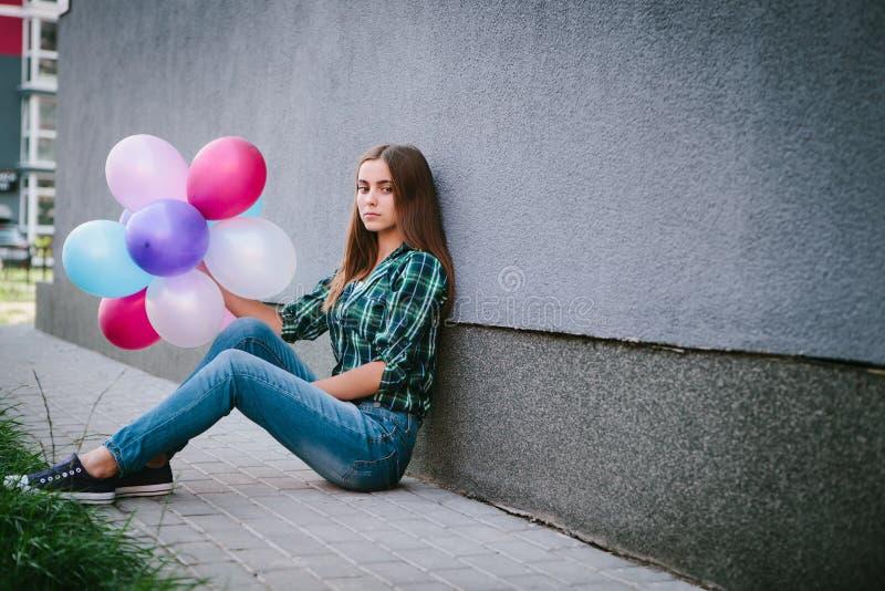 Muchacha triste hermosa que se sienta con los balones de aire coloridos al aire libre, con la pared gris en fondo fotos de archivo libres de regalías