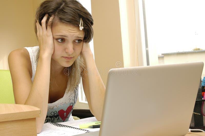 Muchacha triste joven con el ordenador foto de archivo