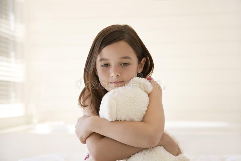 Muchacha triste que abraza a Teddy Bear fotos de archivo
