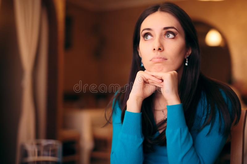 Muchacha triste que espera su fecha en un restaurante imágenes de archivo libres de regalías