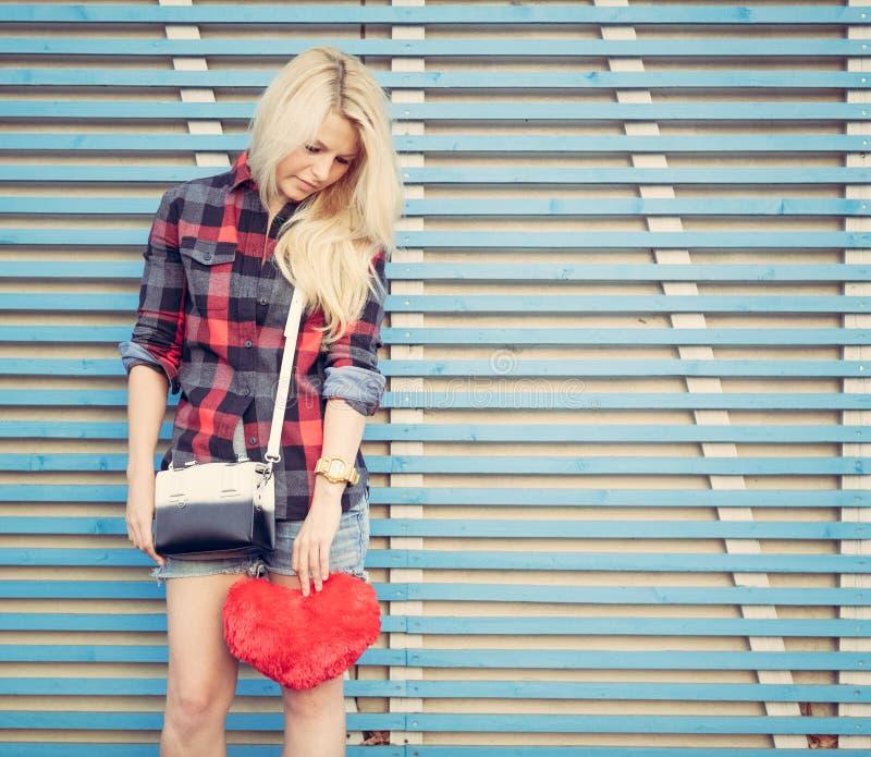 Muchacha triste que lleva a cabo un corazón rojo y soportes cerca de una pared de tablones de madera coloreados fotografía de archivo