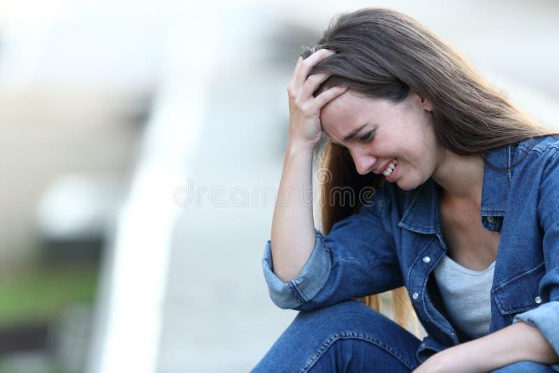 Muchacha triste que llora solamente en la calle imagenes de archivo