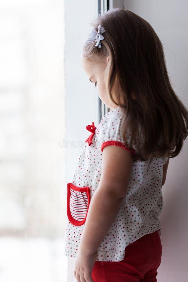 Muchacha triste que mira hacia fuera la ventana fotografía de archivo libre de regalías