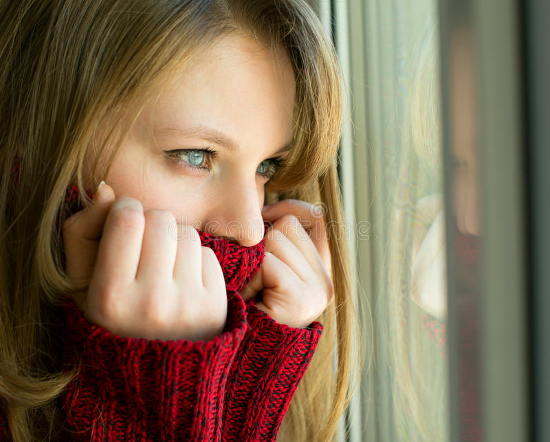 Muchacha triste que mira hacia fuera la ventana que espera a su marido foto de archivo libre de regalías