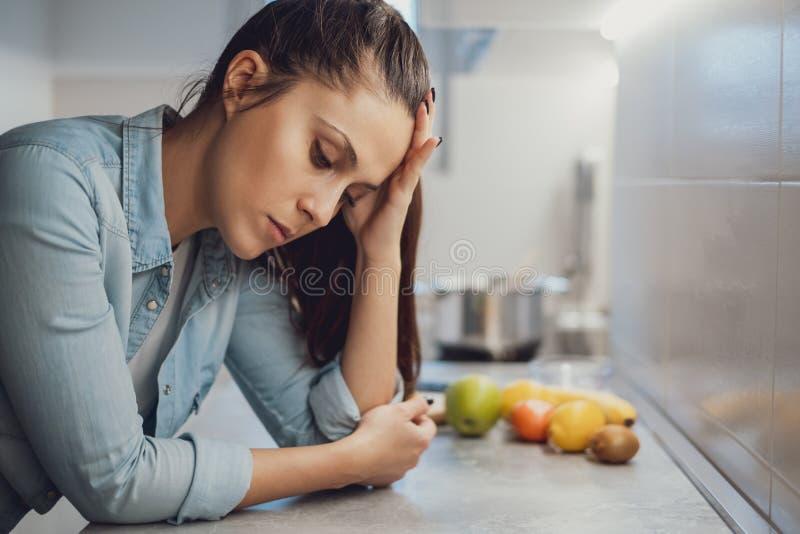 Muchacha triste que se inclina en la encimera de la cocina y que mira abajo imagen de archivo libre de regalías