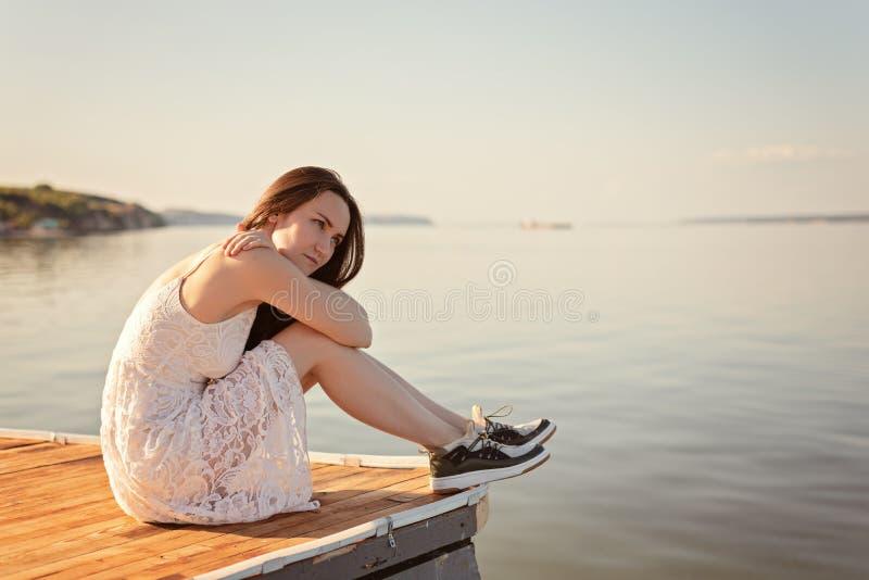 Muchacha triste que se sienta en el embarcadero que abraza sus rodillas, considerando en la distancia, la puesta del sol, soledad imágenes de archivo libres de regalías