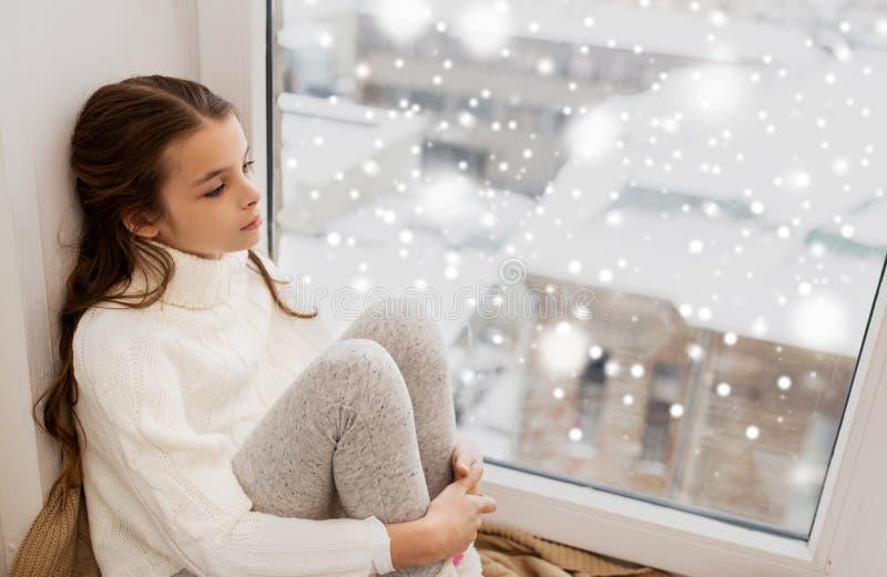 Muchacha triste que se sienta en ventana del travesaño en casa en invierno fotos de archivo