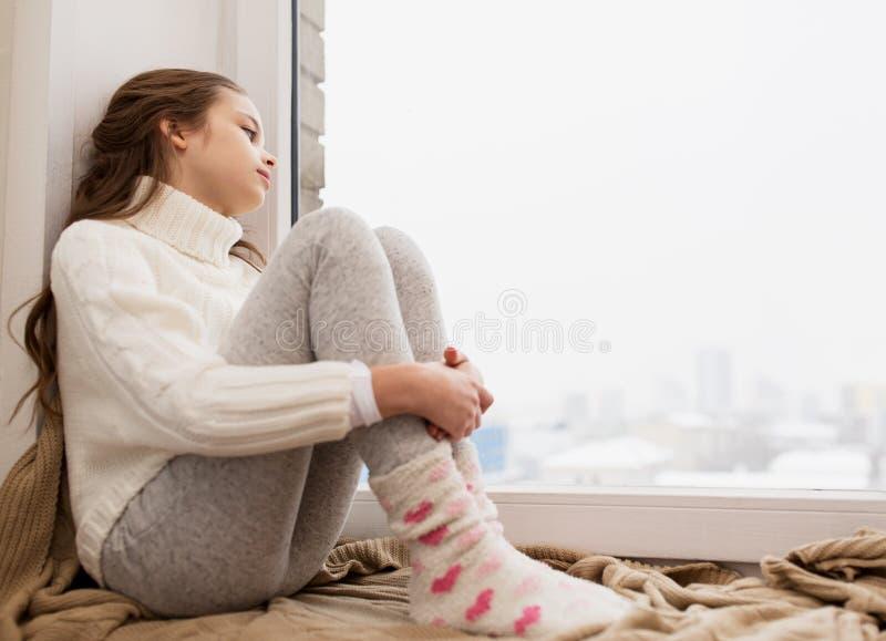 Muchacha triste que se sienta en ventana del travesaño en casa en invierno imagenes de archivo