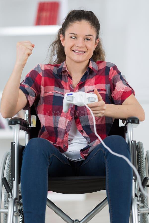Muchacha triunfante en palanca de mando del ordenador de la tenencia de la silla de ruedas imagenes de archivo