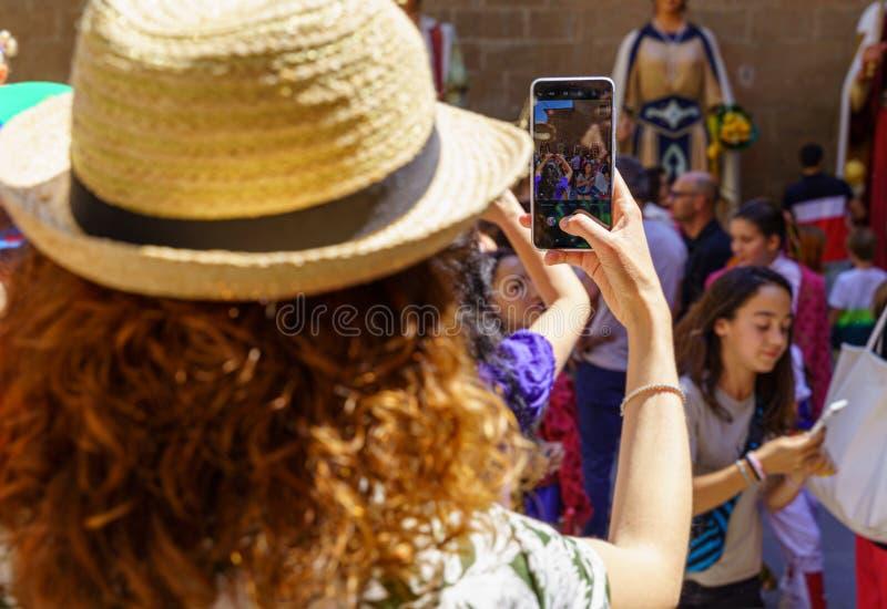 Muchacha turística que toma una imagen con un smartphone de Giants y de cabezas grandes en Cataluña, España fotografía de archivo libre de regalías