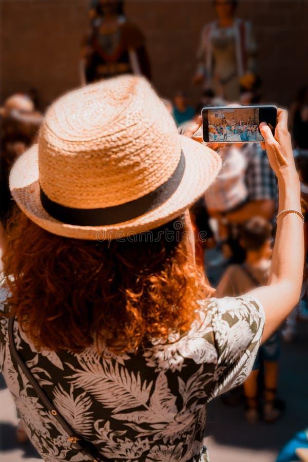 Muchacha turística que toma una imagen con un smartphone de Giants y de cabezas grandes en Cataluña, España fotos de archivo