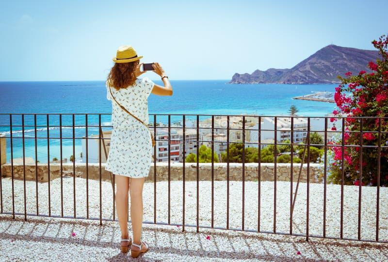 Muchacha turística que toma una imagen con un smartphone del mar Mediterráneo en Altea, Alicante, España fotografía de archivo libre de regalías