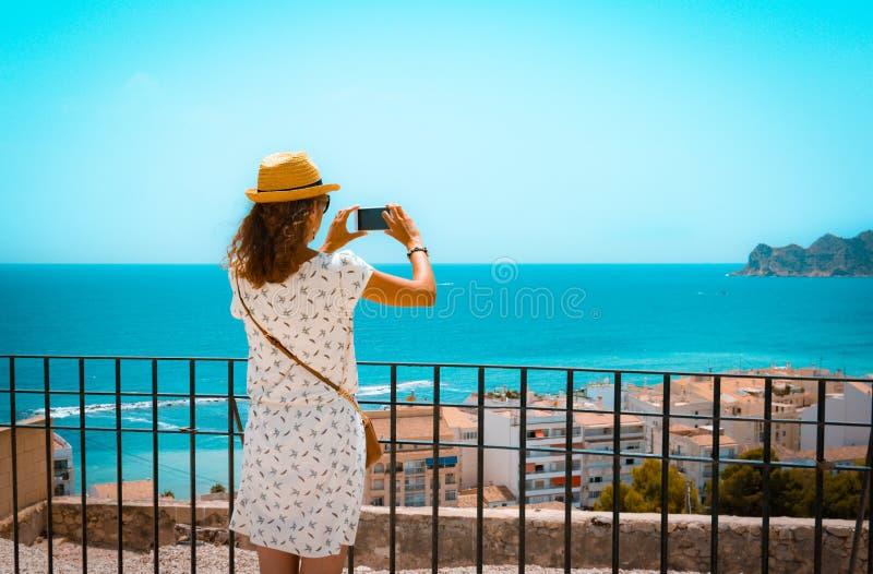 Muchacha turística que toma una imagen con un smartphone del mar Mediterráneo en Altea, Alicante, España imagenes de archivo