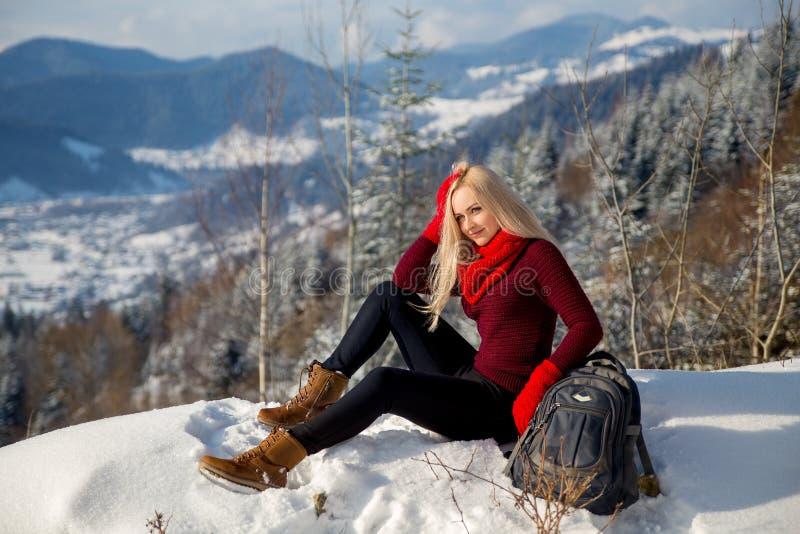 Muchacha turística rubia hermosa que se sienta en la roca fotos de archivo libres de regalías