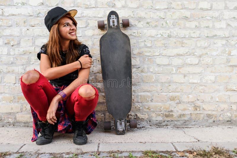 Muchacha urbana linda con sentarse que se sienta del longboard al lado de una pared de ladrillo imagen de archivo libre de regalías