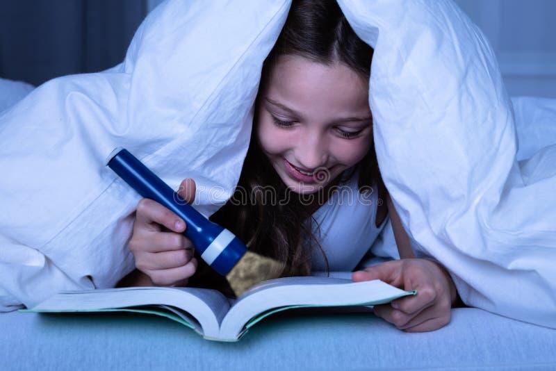 Muchacha usando la linterna mientras que libro de lectura fotografía de archivo libre de regalías