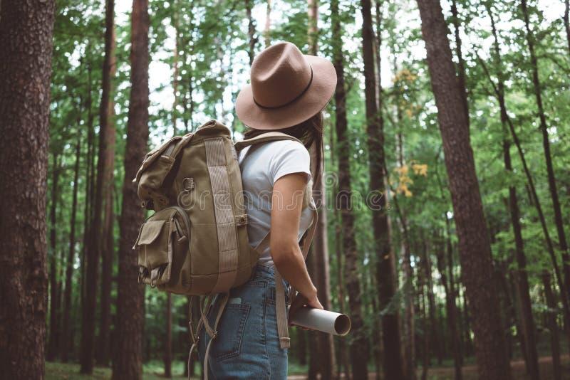 Muchacha valiente del inconformista que viaja solamente y que mira alrededor en bosque en mapa de ubicación de la mochila y del c fotos de archivo libres de regalías