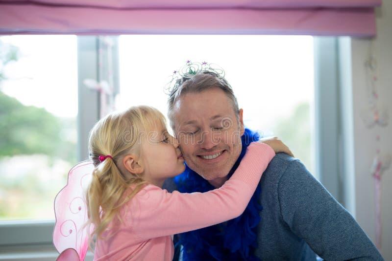 Muchacha vestida como hada que besa a su padre fotografía de archivo libre de regalías